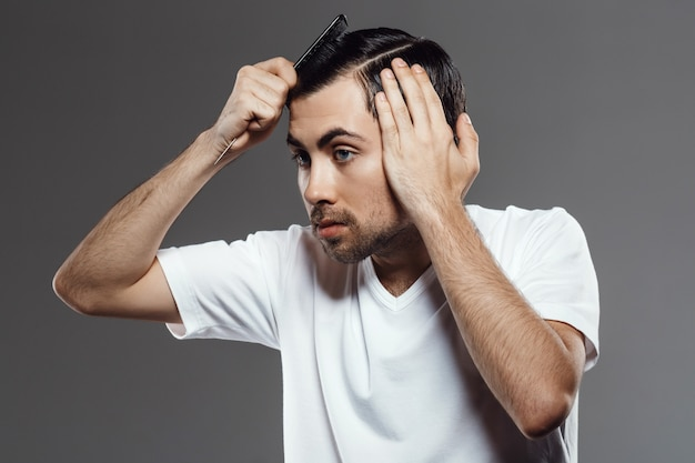 Молодой красавец расчесывает волосы, делает стрижку