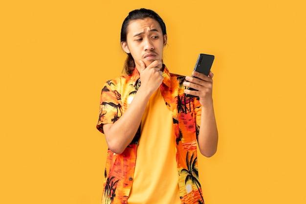 Молодой красавец смущен со смартфоном в руке