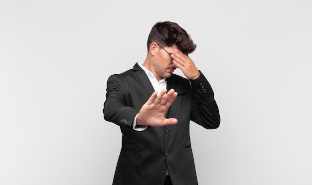 Молодой красавец сжимает лицо рукой и поднимает другую руку, чтобы остановиться, отказываясь от фотографий или изображений