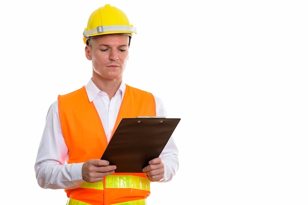 Young handsome man construction worker reading on clipboard