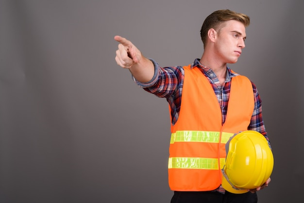Young handsome man construction worker with blond hair on grey wall
