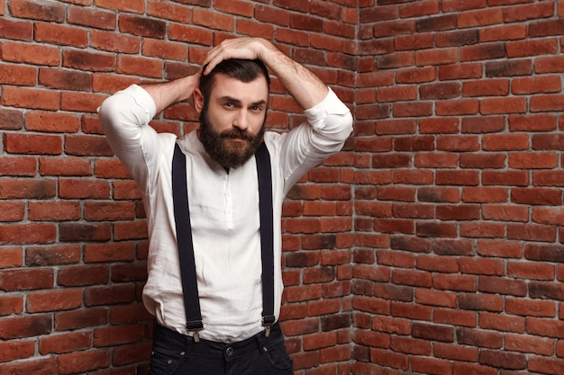 Young handsome man correcting hairstyle on brick wall.