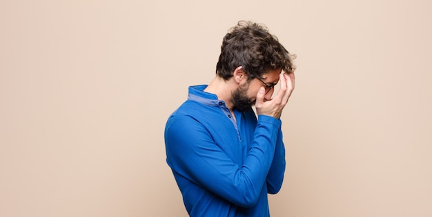 Young handsome man covering eyes with hands with a sad, frustrated look of despair, crying, side view on flat wall