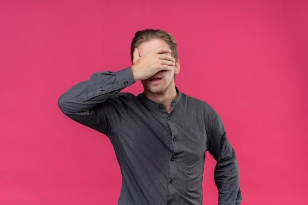 ピンクの壁の上に立っている彼の手で目を覆っている若いハンサムな男