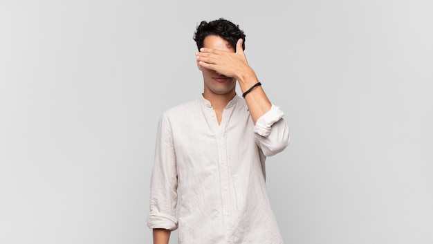 片手で目を覆っている若いハンサムな男は、恐怖や不安を感じ、不思議に思ったり、盲目的に驚きを待っています