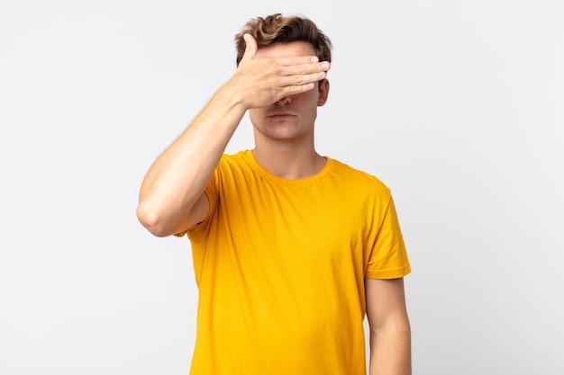 恐怖や不安を感じ、不思議に思ったり、盲目的に驚きを待っている片手で目を覆っている若いハンサムな男