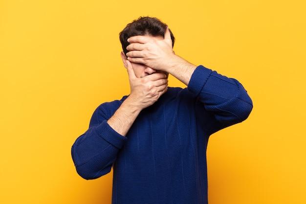 Молодой красавец закрыл лицо обеими руками, говоря «нет» в камеру! отказ от фотографий или запрет на фотографии