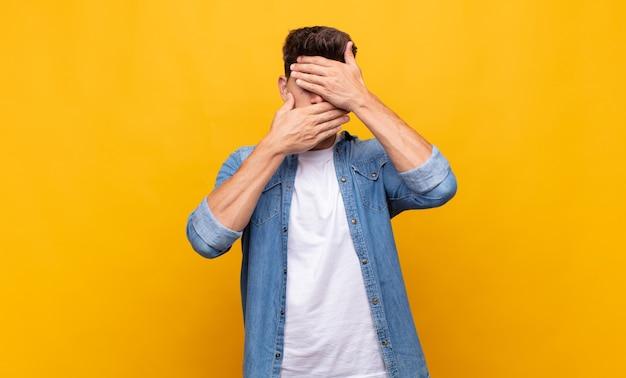 Молодой красавец закрыл лицо обеими руками, говоря «нет» в камеру!
