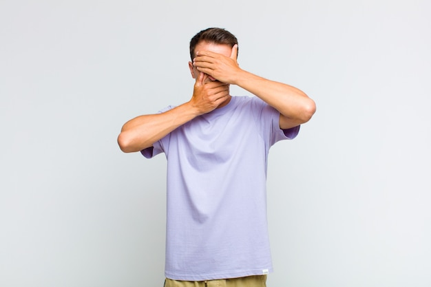 Young handsome man covering face with both hands saying no