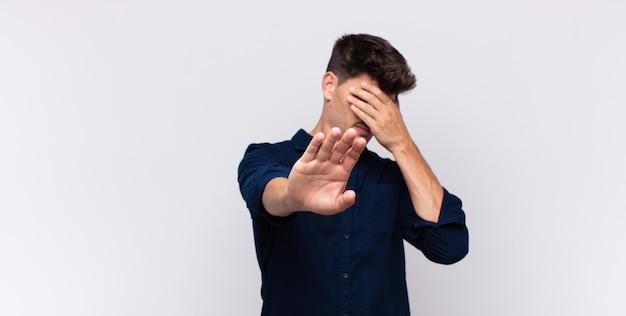 Молодой красавец закрывает лицо рукой и поднимает другую руку, чтобы остановить камеру, отказываясь от фотографий или изображений