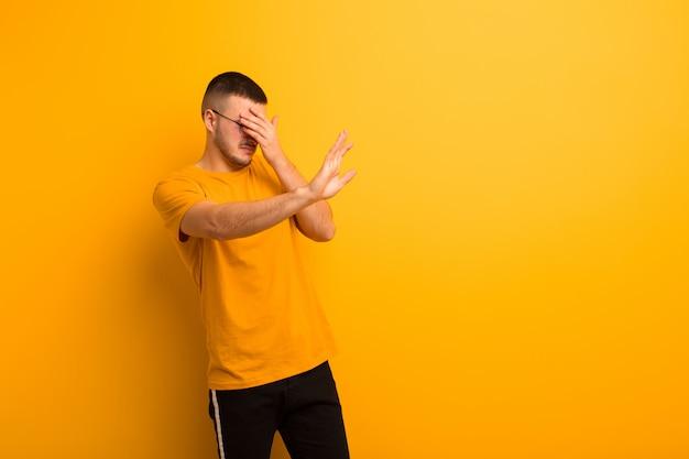 Молодой красивый мужчина закрывает лицо рукой и поднимает другую руку вперед, чтобы остановиться, отказываясь от фотографий или картинок у плоской стены