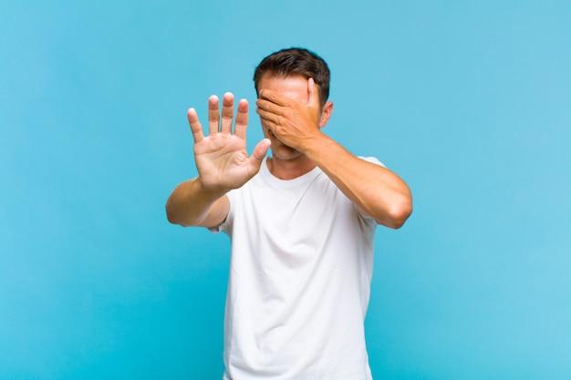 顔を手で覆い、もう一方の手を前に出して停止し、写真や写真を拒否する若いハンサムな男