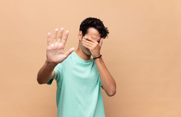 Young handsome man covering face with hand and putting other hand up front to stop camera, refusing photos or pictures