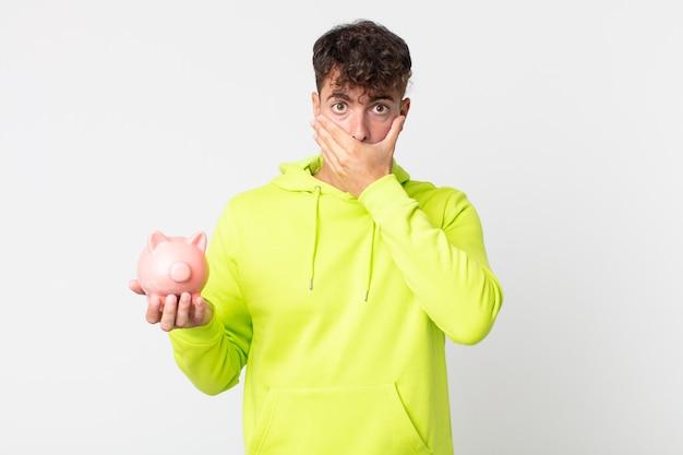 ショックを受けて貯金箱を持って手で口を覆う若いハンサムな男