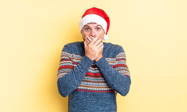 ショックを受けた手で口を覆う若いハンサムな男。クリスマスのコンセプト