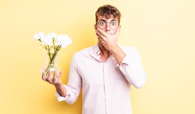 ショックを受けた手で口を覆う若いハンサムな男。花のコンセプト