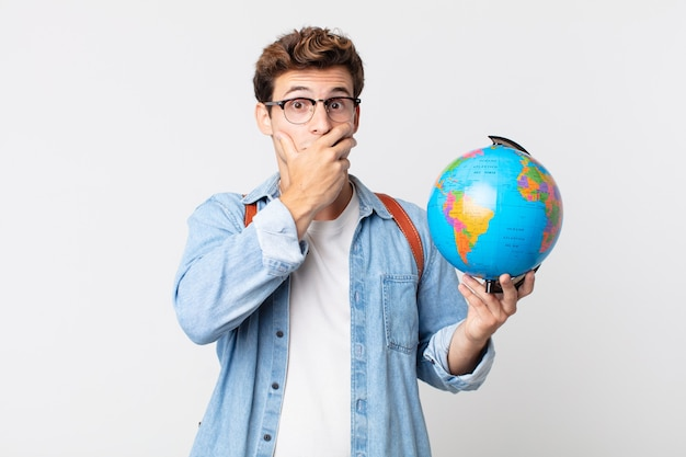 ショックを受けた手で口を覆う若いハンサムな男。世界の地球地図を持っている学生