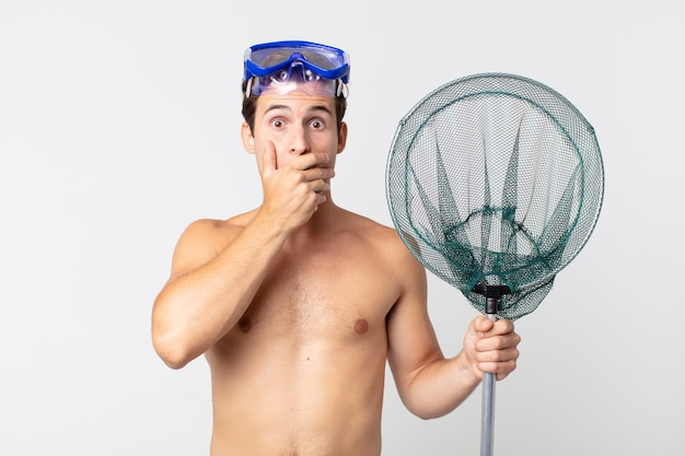 Young handsome man covering mouth with hands with a shocked with goggles and a fishing net