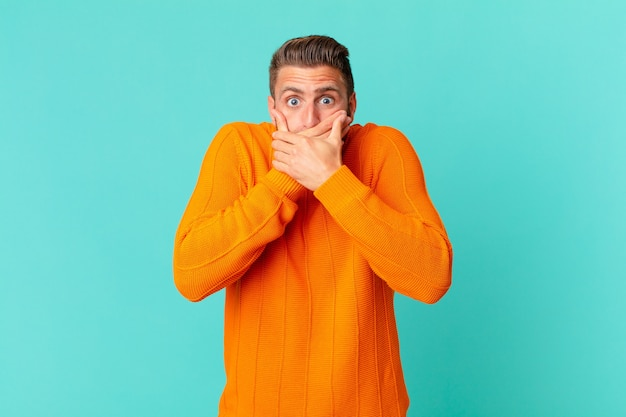Young handsome man covering mouth with hands with a shocked