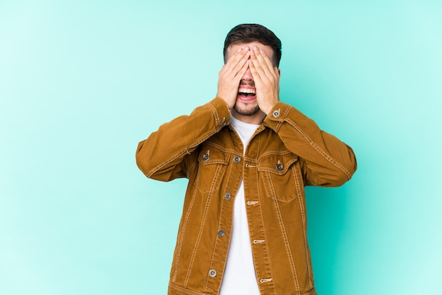 Young handsome man covers eyes with hands, smiles broadly waiting for a surprise.