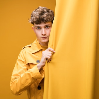 Young handsome man next to a curtain in a yellow scene