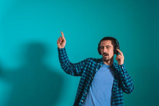 파란색 배경에 헤드폰을 끼고 음악을 들으며 춤을 추고 노래하는 젊은 미남
