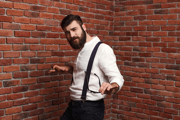 Young handsome man dancing posing on brick wall.