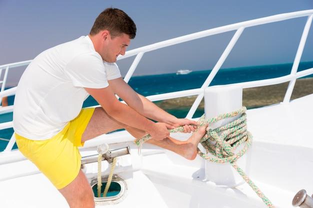 젊고 잘생긴 남자는 화창한 여름날 요트에 밧줄을 부지런히 고정하고 아름다운 바다를 배경으로 한다