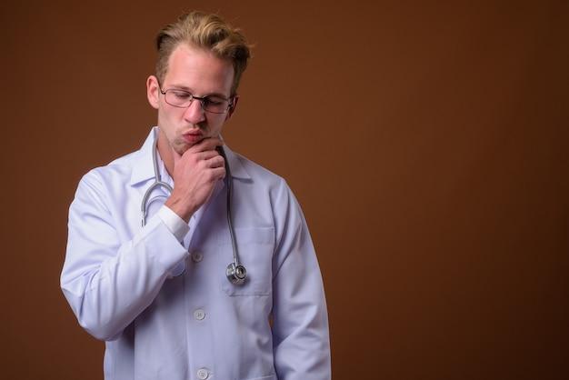 茶色の表面に対して若いハンサムな男医師
