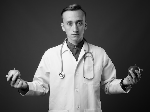 Young handsome man doctor against gray wall. black and white