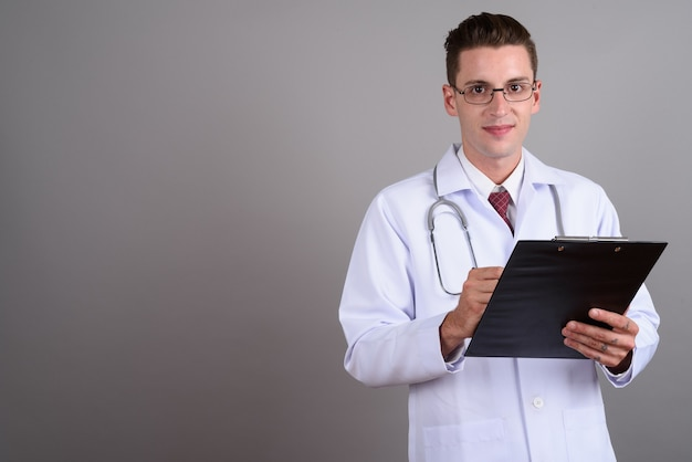 Young handsome man doctor wearing eyeglasses on gray