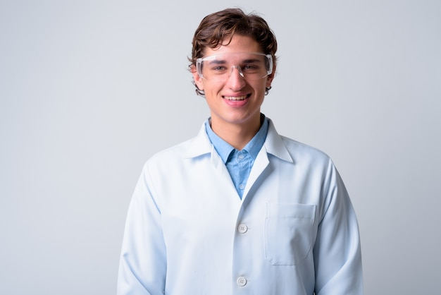 Young handsome man doctor wearing protective glasses
