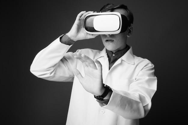 Молодой красавец доктор носить гарнитуру виртуальной реальности против серой стены. черное и белое