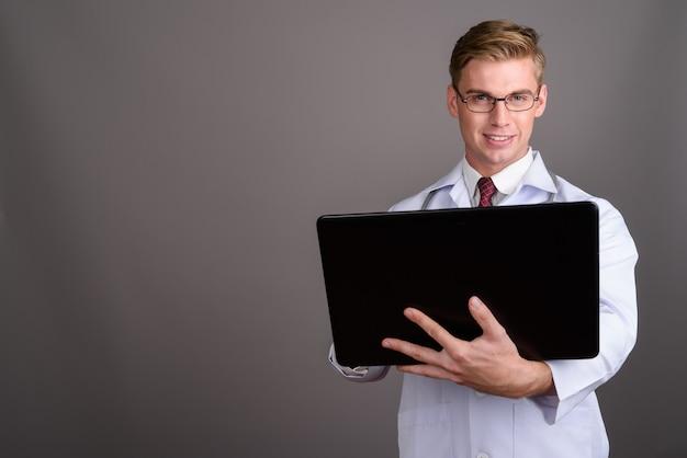 Молодой красивый мужчина доктор со светлыми волосами на серой стене