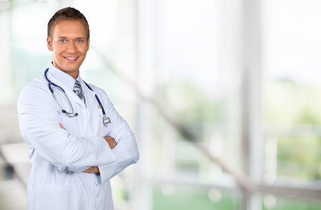 Young handsome man doctor  with blurred hospital interior on background