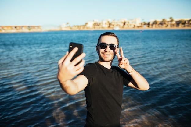 ビーチでスマートフォンで自画像の勝利のサインをしている若いハンサムな男