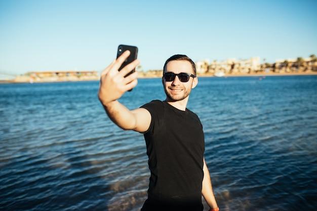 ビーチでスマートフォンで自画像をやっている若いハンサムな男