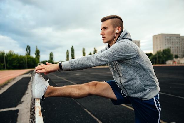 Молодой красивый человек делает упражнения, разыгрывая ноги, слушая музыку