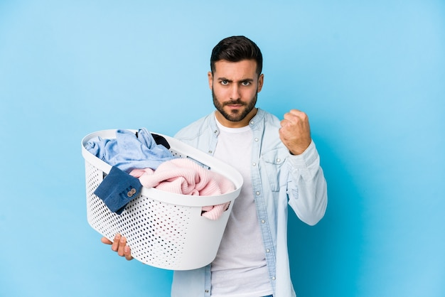 Young handsome man doing laundry isolated showing fist , aggressive facial expression.