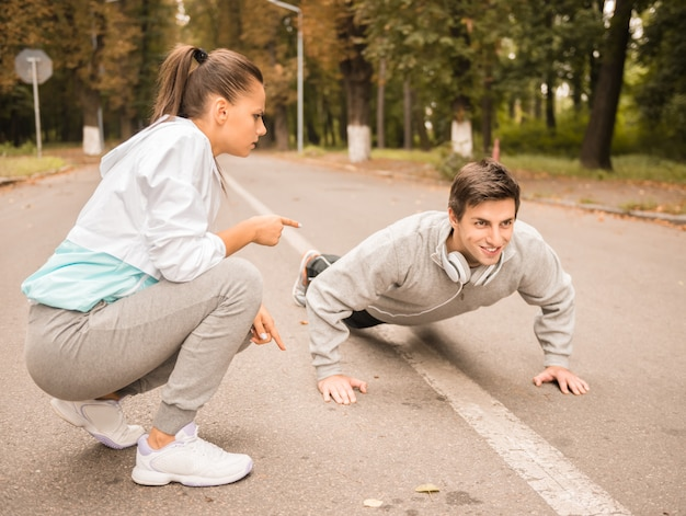 Young handsome man doing push ups with trainer outdoor.