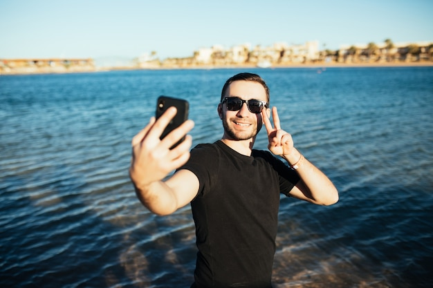 Young handsome man doing a self-portrait victory sign with smartphone on the beach