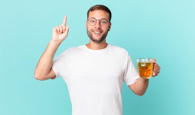 맥주 한 잔을 마시는 젊은 잘생긴 남자