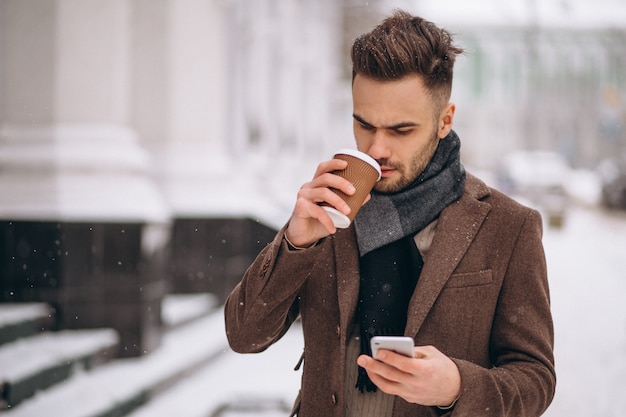 Молодой красивый мужчина пьет кофе и разговаривает по телефону