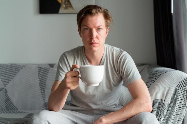 自宅のリビングルームでコーヒーを飲む若いハンサムな男