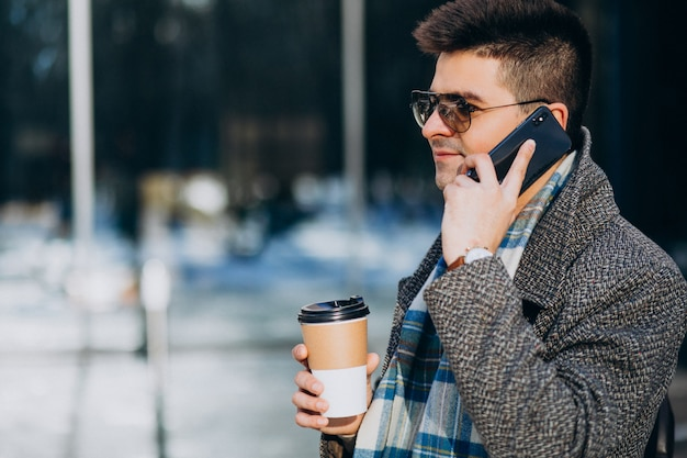 Young handsome man drinking coffee outside and using phone
