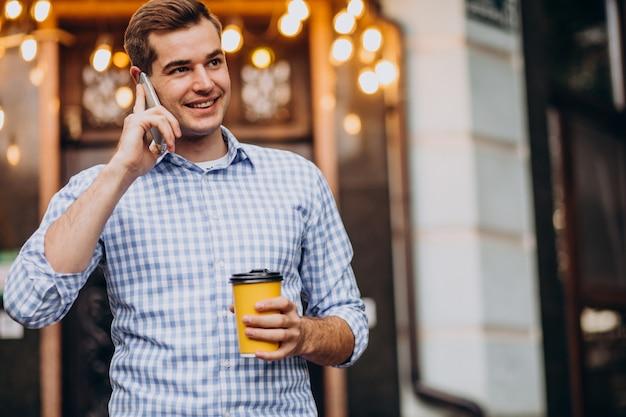 Молодой красивый мужчина пьет кофе на улице