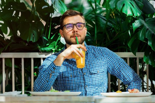 カフェでジュースを飲む若いハンサムな男