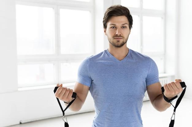 체육관에서 저항 고무 밴드와 함께 운동하는 동안 젊은 잘 생긴 남자. 이두근 컬 운동.