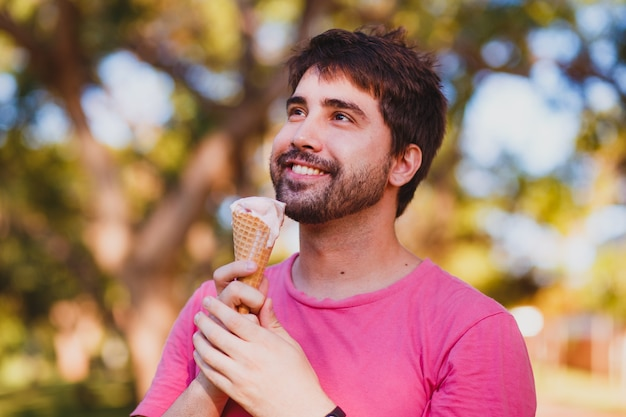 Young handsome man eating ice cream in the park