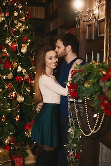 クリスマスのために飾られたインテリアでゴージャスなモデルの女性を抱きしめてキスする若いハンサムな男
